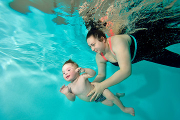 Instructor, mom teaches and helps the baby to swim underwater in the pool. Portrait. The view from under the water. Landscape orientation