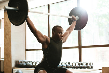 Strong muscular african sportsman with barbell at the gym Wall mural