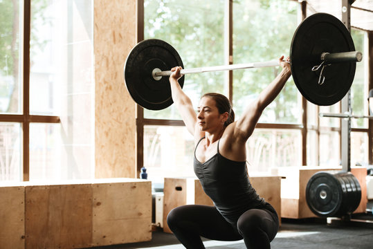 Sporty concentrated woman exercising with barbell