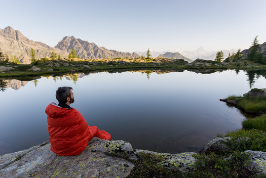 Young adult man in red sleeping bag near mountain lake with reflection at dawn in summer outdoor.