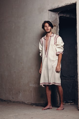 Super male model giving a nice pose for indoor photography. Wearing a full sleeve long neck linen lounge dress without pants. Looks like he found something new inside the scrappy room.