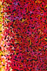 sequins  texture. Red, orange and pink round sequins background. iridescent sequins texture.