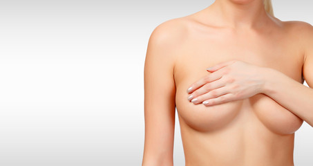 Woman controlling breast for cancer against a grey background with copyspace. Female healthcare concept