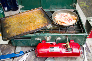 Gas camping stove and sizzling bacon in fry pan