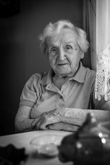 Monochrome portrait of elderly woman sitting at the table.