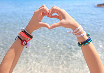 model advertising greek jewelry on the beach - creating heart symbol with her hands
