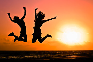 Couple Jumping in the Air with Sunset in the Background