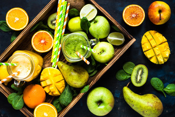 Green and yellow smoothie in mason jar and fresh fruit. Top view on dark concrete table.