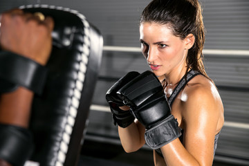 Woman fighter ready to throw a punch with trainer teacher holding pads for boxing session
