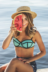 Sweet summertime tastes. Cheerful and young woman in hat and swimsuit keeping watermelon slice against half part of her face while sitting on the beach.