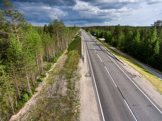 Empty asphalt country road in northern Karelia. Thunderclouds over forest. Russia