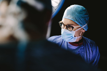Female surgeon with team performing surgery