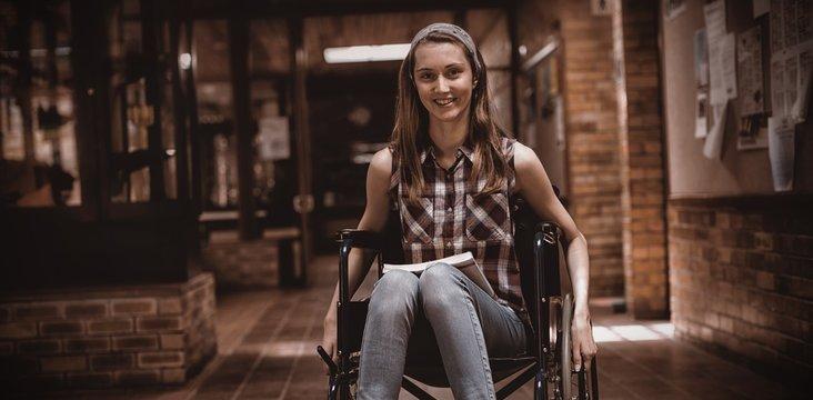 Disabled schoolgirl on wheelchair in corridor at school