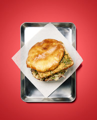 tofu sandwich on metal tray, on red background, studio