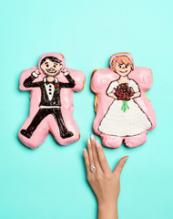 specialty bride and groom donuts with hand in-frame, on turquoise background, studio