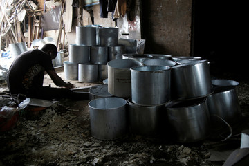 A man works next to buckets made with recycled sheet metal at his recycling warehouse in Abidjan, Ivory Coast