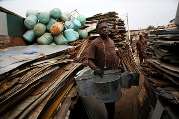 A worker holds buckets made with recycled sheet metal as he walks between metalic wastes at his recycling work place  in Abidjan, Ivory Coast
