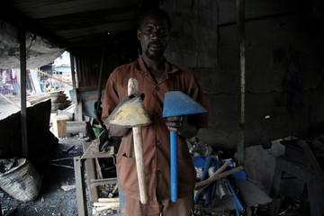 """A worker holds """"Dabas"""" west african hoe made with metalic wastes at his recycling warehouse in Abidjan, Ivory Coast"""