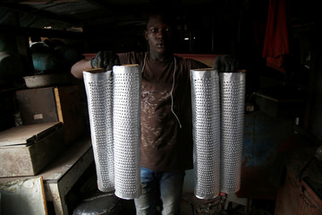 A man holds kitchen tools made with recycled sheet metal at his recycling warehouse in Abidjan, Ivory Coast