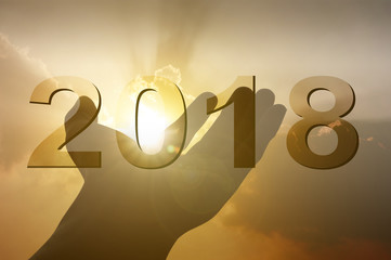 Hand on sunset background with text 2018 celebration christmas happy new year art abstract background