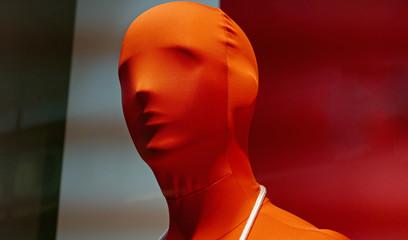 Kopf einer männlichen Schaufensterpuppe in einem roten Ganzkörperanzug