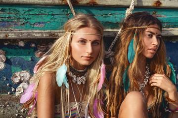 two beautiful young woman in bikini sitting on the beach at old fishing boat