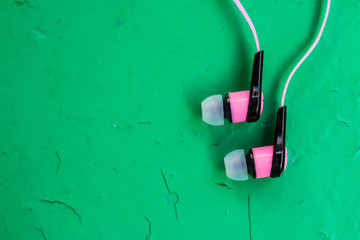 White, pink stereo earphones on wooden green background, copy space for text
