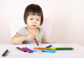Adorable child drawing with colorful crayons and smiling, with the copy space