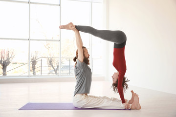 Young couple practicing yoga indoors