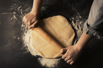 Woman rolling out raw dough on dark table