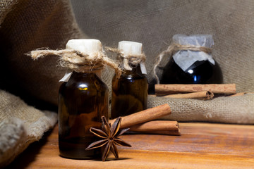 Essential oil of star anise in a small bottle on wooden background