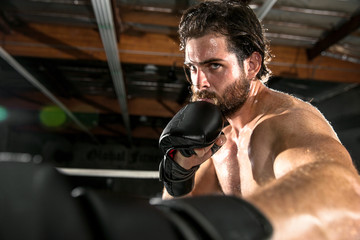 Handsome muscular MMA fighter throwing a punch, jab, hook, during a match