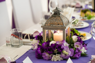 wedding banquet table in white and purple colours decorated lanterns and candles