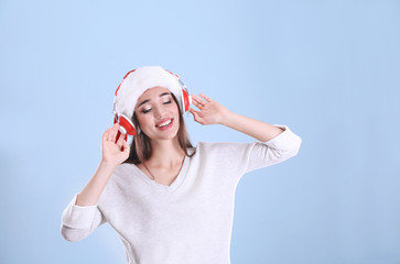 Beautiful young woman in Santa hat listening to Christmas music on color background