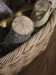 Isolated Close View of Firewood and Fireplace Broom in a Basket  on a Hardwood Floor