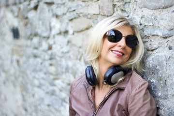 portrait of  blond woman smiling  with headphones to the neck