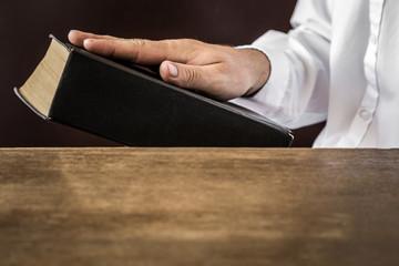 Man's hand swearing on the bible. Taking an oath.