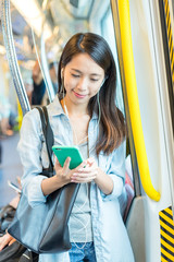 Woman listen to music and using cellphone on train