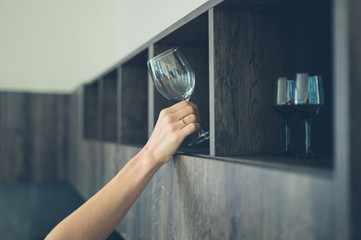 Young woman getting wine glass in kitchen