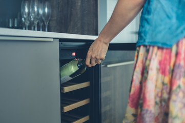 Woman getting bottle of wine from cooler