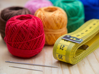 colored woolen thread and needles and meter close up on a wood background