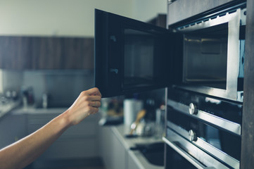 Young woman opening the microwave