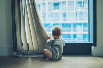 LIttle baby playing with curtain in apartment
