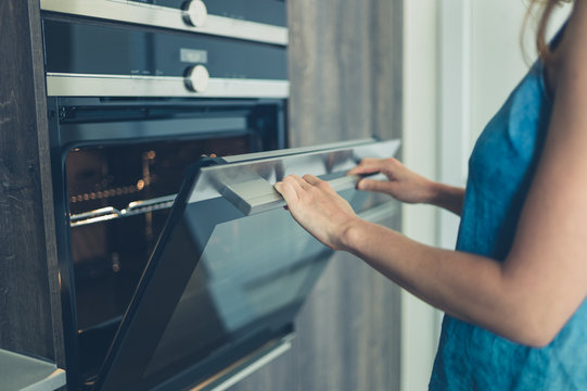 Young woman opening the oven