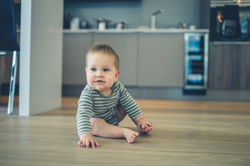 Little baby on kitchen floor