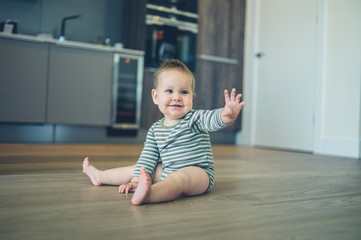 Little baby on kitchen floor waving