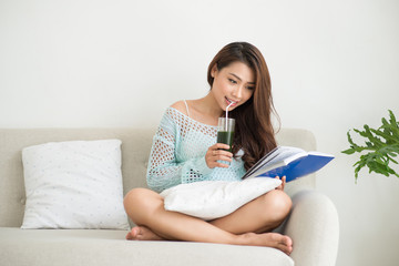 Woman relaxing on sofa in livingroom enjoying reading a book and drinking coffee.