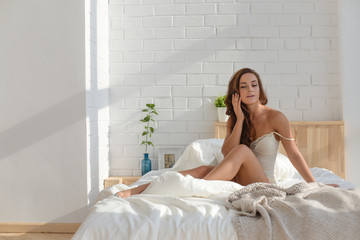 Young lady at home in bedroom at early morning