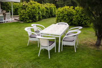 White garden furnituse sofa armchair table on the lawn