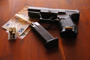 9mm pistol on a desk with money and a loaded magazine